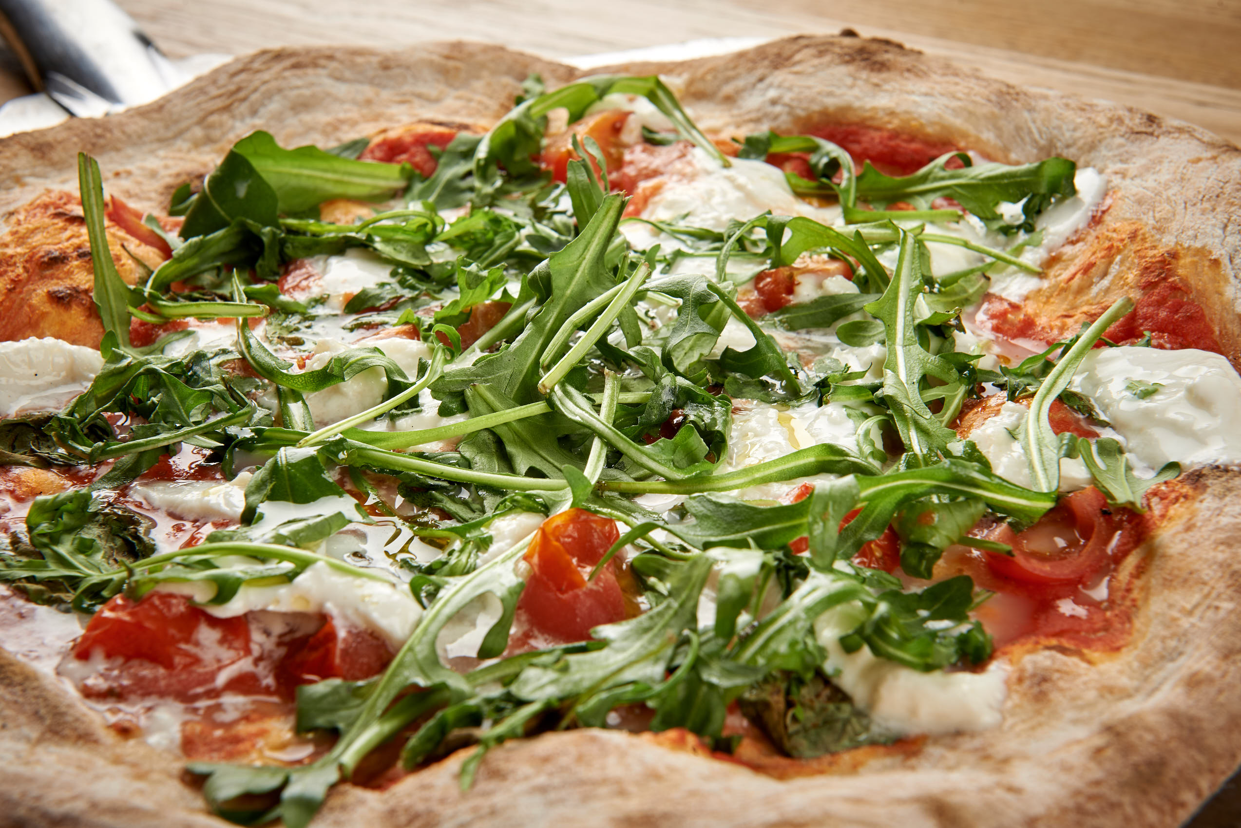 Pizza with ruccola, tomatoes and mozerella photo by Marcel Tiedje