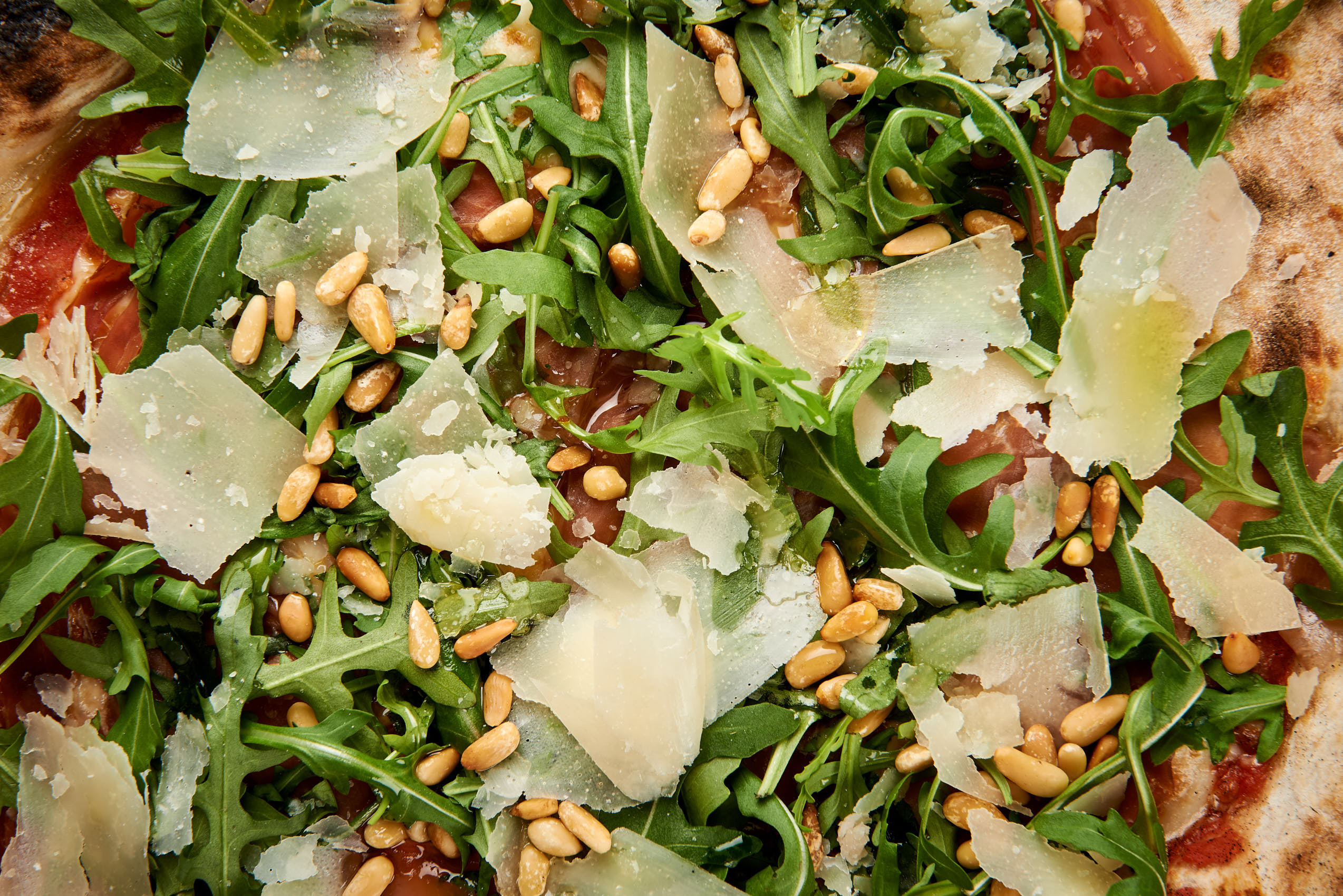 Parmapizza with pine nuts closeup photo by Marcel Tiedje