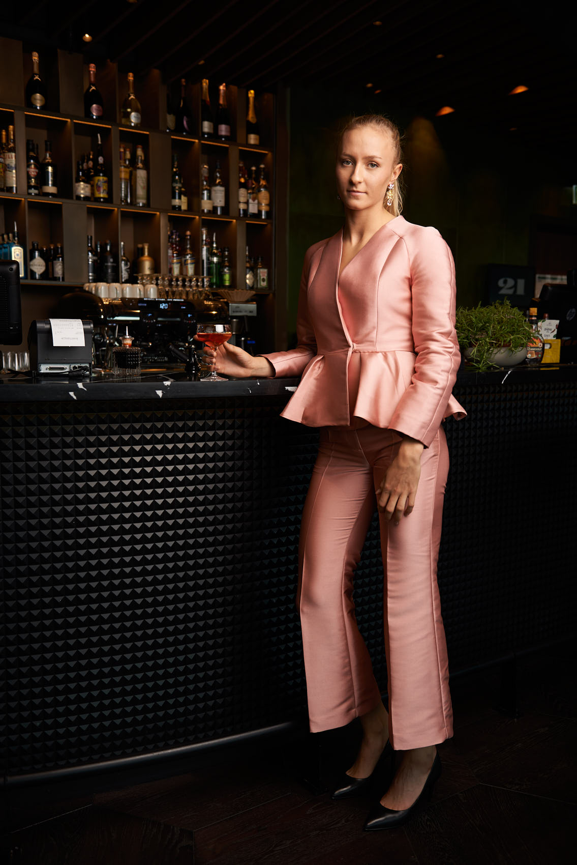 Scandinavian blonde girl standing at the cocktail bar in pink party suit photo by Marcel Tiedje