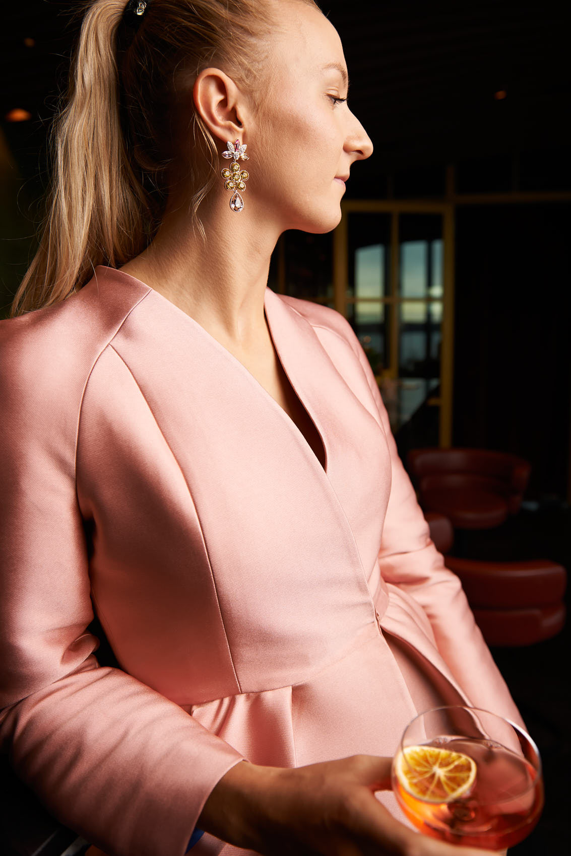 Høyer pink party suit with earrings and cocktail photo by Marcel Tiedje