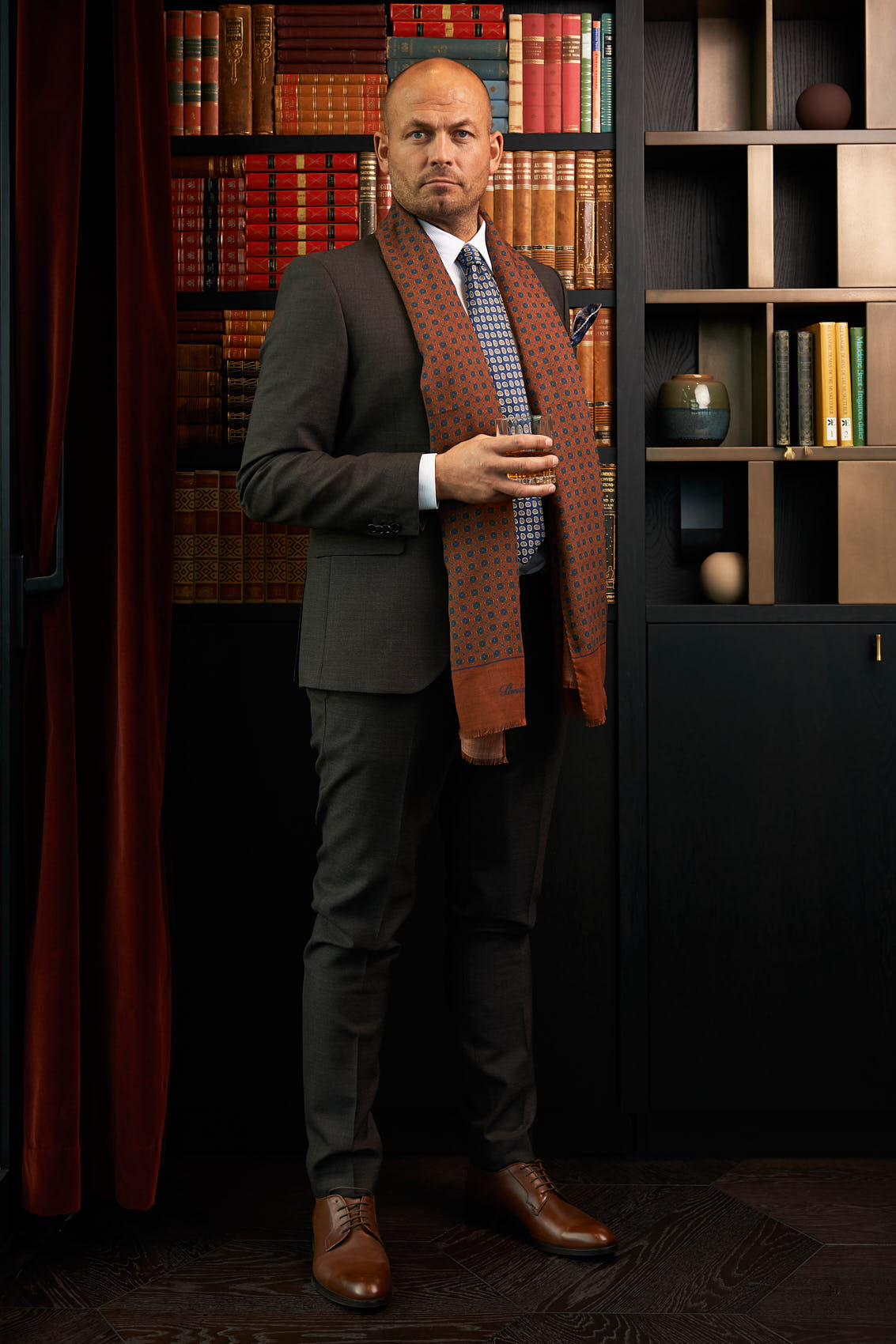 Gentlemen in brown suit holding a cognac glass with a book wall background for Høyer photo by Marcel Tiedje