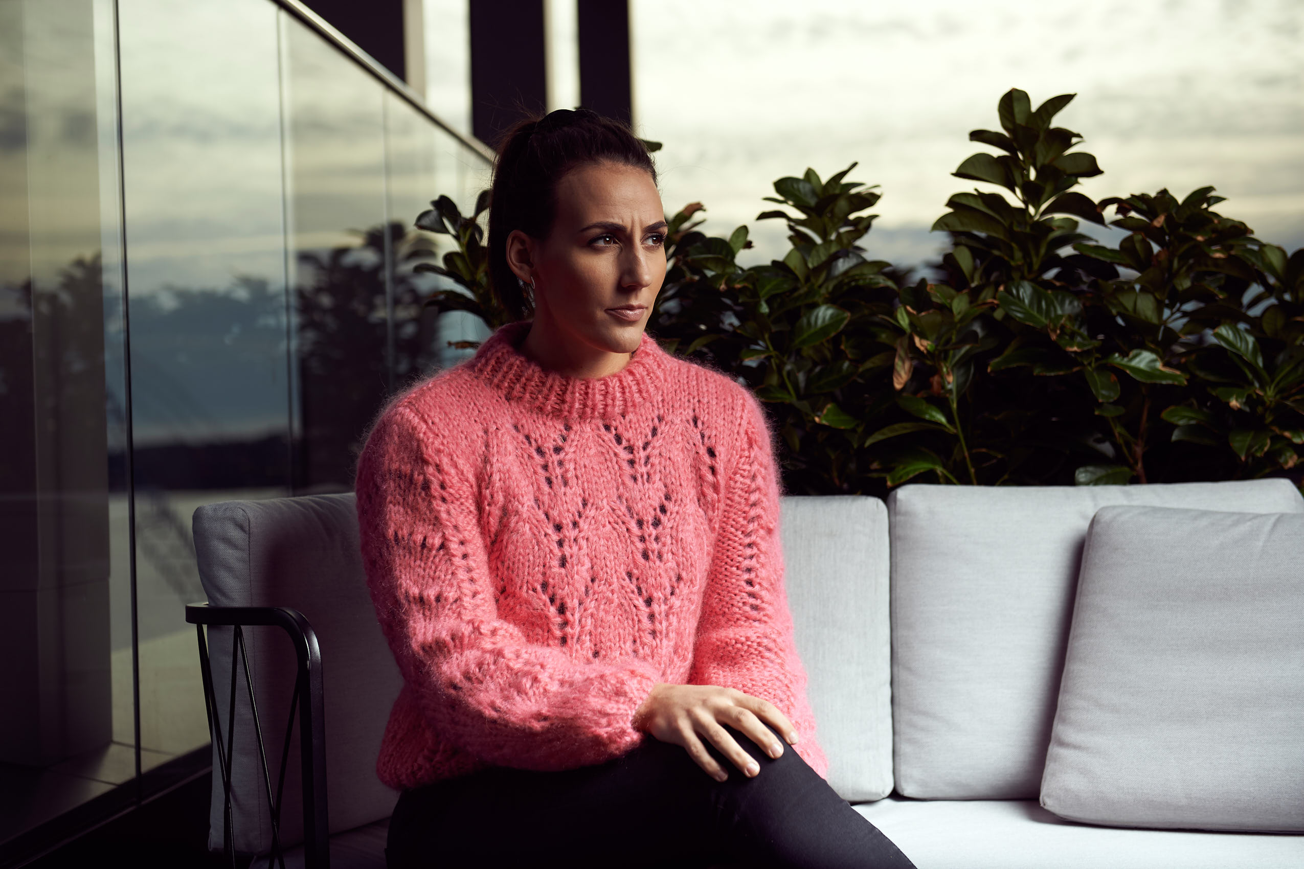 Woman in pink sweater sitting on grey couch at outdoor terrace photo by Marcel Tiedje