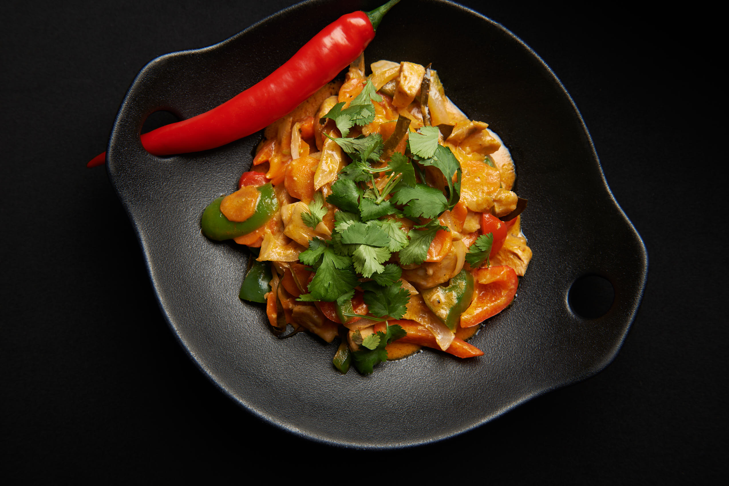 Thai curry chicken with chili and vegetables photo by Marcel Tiedje